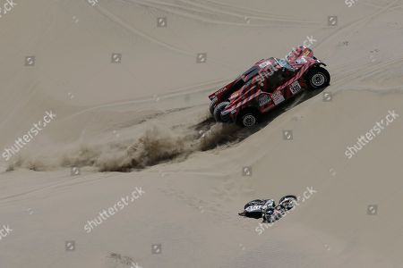 Stock Picture of Driver Eugenio Amos, of Italy, and co-driver Sebastien Delaunay, of France, race their Ford pass the abandoned KTM motorbike of Walter Nosiglia Jager, of Bolivia, during the 4th stage of the 2018 Dakar Rally in San Juan de Marcona, Peru