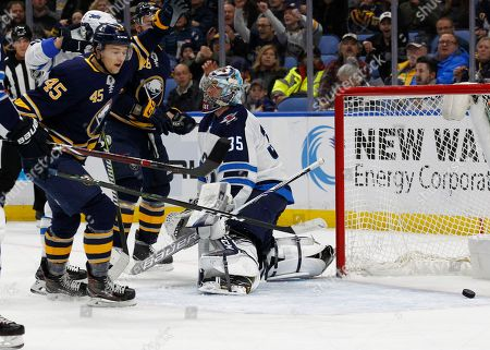 Buffalo Sabres defenseman Brendan Guhle (45) watches the puck go past Winnipeg Jets goalie Steve Mason (35) during the first period of an NHL hockey game, in Buffalo, N.Y