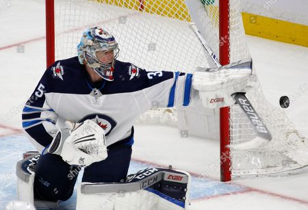 Winnipeg Jets goalie Steve Mason (35) makes a stick save during the third period of an NHL hockey game against the Buffalo Sabres, in Buffalo, N.Y