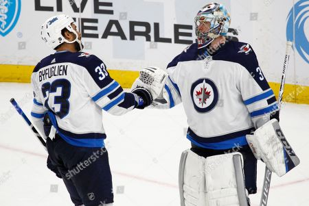 Winnipeg Jets forward Dustin Byfuglien (33) and goalie Steve mason (35) celebrate a 7-4 victory over the Buffalo Sabres following the third period of an NHL hockey game, in Buffalo, N.Y