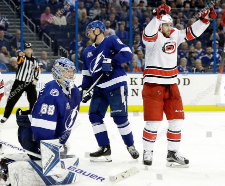 Stock Photo of Andrei Vasilevskiy, Anton Stralman, Elias Lindholm. Carolina Hurricanes center Elias Lindholm, right, of Sweden, celebrates his goal against Tampa Bay Lightning goaltender Andrei Vasilevskiy, left, and Anton Stralman, center, during the third period of an NHL hockey game, in Tampa, Fla. The Lightning won 5-4