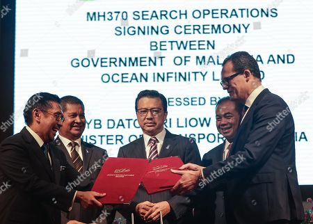 Malaysia Transport Minister Liow Tiong Lai (C) looks at the exchange of documents between Director General Civil Aviation Malaysia Azharuddin Abdul Rahman (L) and CEO Ocean Infinity Limited Oliver Plunkett (R) during a signing ceremony between the Malaysian government and Ocean Infinity Limited at the Transport Ministry building, in Putrajaya, Malaysia, 10 January 2018. The MH370 went missing from radar on 08 March 2014, while traveling from Kuala Lumpur, Malaysia to Beijing, China with 239 people aboard. Authorities from the governments of Australia, China and Malaysia suspended the search for the plane in January 2017 after conducting an extensive underwater search of a 120,000 square-kilometer area in the Indian Ocean.