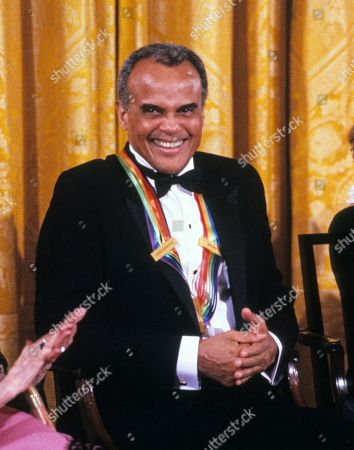 Singer and actor Harry Belafonte listens as first lady Barbara Bush makes remarks during a ceremony for 1989 Kennedy Center Honorees in the East Room of the White House, in Washington, DC. The 1989 honorees are: actress and singer Mary Martin, dancer Alexandra Danilova, singer and actor Harry Belafonte, actress Claudette Colbert, and composer William Schuman.