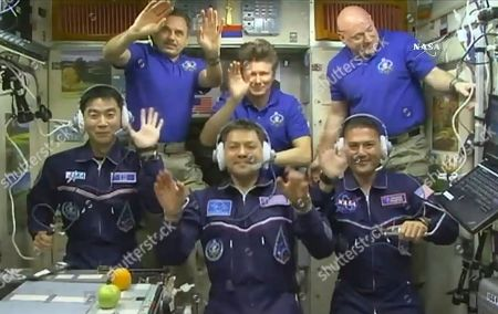 In this image taken from video from NASA, astronauts, front row from left, Kimiya Yui, of Japan, Oleg Kononenko, of Russia, and Kjell Lindgren, of the United States, wave after they boarded the International Space Station, early . Joining the new crew are, rear row from left, astronauts Mikhail Kornienko and Gennady Padalka, from Russia, and Scott Kelly, of the U.S