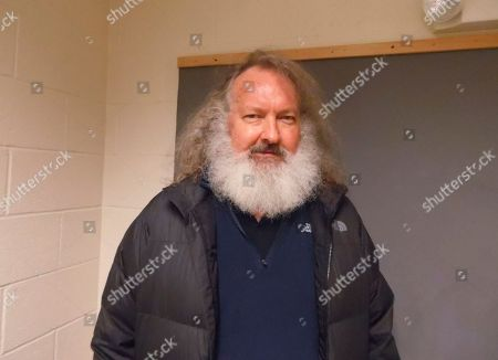 """In a photo provided by the Vermont State Police, actor Randy Quaid stands in the Vermont State Police barracks in St. Albans, Vt., . State Police say Quaid has been taken into custody while trying to cross from Canada into the United States. State Police say the """"Independence Day"""" actor was detained by troopers at the Highgate Springs port of entry, days after Canadian officials said he would be deported. Quaid is wanted in Santa Barbara, Calif., to face felony vandalism charges filed in 2010 after he and his wife, Evi, were found squatting in a guesthouse of a home they previously owned"""