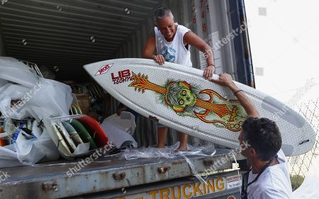 Stock Photo of Robyn Cohen, National Director of Waves For Change surf therapy organisation (L) offloads a container of over 700 surfboards donated by US surfers for children in Africa as they arrive in Cape Town, South Africa, 11 January 2018. The #cantstealourvibe surfboard drive was started by US professional surfer Patrick Gudauskas and his brothers Tanner and Dane and South African professional surfer Mikey February to help support  African surf therapy foundations Waves For Change and Surfers Not Street Children. Waves For Change is a Laureus award winning surf therapy program providing a child friendly mental health service to at risk youth living in unstable communities with centres in Liberia, Somalia and South Africa and aim to open another 10 centres across Africa in 2018.