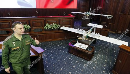 Stock Photo of A Russian military gestures nearby the  drones allegedly used by militants acting in Syria on early hours of 06 January 2018 to strike Russian bases in Syrian Hmeimim and Tartus are on display at the Russian Defence Ministry headquarters in Moscow, Russia, 11 January 2018.