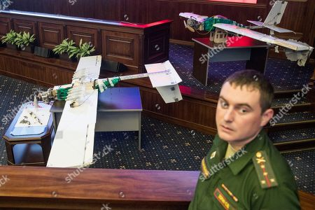 A Russian officer stands next to drones that attacked the Russian air base in Syria and were captured by the Russian military are displayed at a briefing in the Russian Defense Ministry in Moscow, Russia, . Saturday's, Jan.6, 2018 raid against the Hemeimeem air base and a Russian naval facility in Tartus involved 13 drones, seven of the drones were shot down by air defense systems and the remaining six were forced to land, according to the Russian Defense Ministry