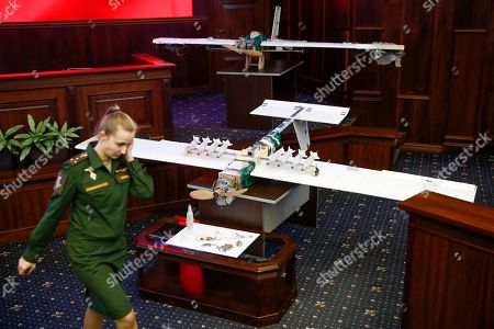 A Russian officer walks next to drones that attacked the Russian air base in Syria and were captured by the Russian military are displayed at a briefing in the Russian Defense Ministry in Moscow, Russia, . Saturday's, Jan.6, 2018 raid against the Hemeimeem air base and a Russian naval facility in Tartus involved 13 drones, seven of the drones were shot down by air defense systems and the remaining six were forced to land, according to the Russian Defense Ministry