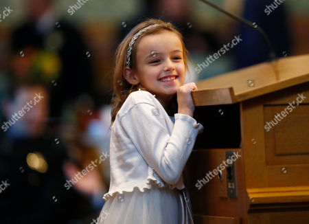 Seven-year-old Ashley Scott of Colorado Springs, Colo., smiles as she steps to the podium for a photograph before the State of the State address to a joint assembly, in the State Capitol in Denver. In his speech, Colorado Gov. John Hickenlooper cited the girl's efforts to round up clothing for homeless people in Colorado Springs through an organization called Kids Care Too