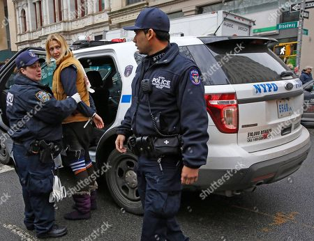 A New York City police officer leads protester Monica Hunken into a squad car after she was arrested along with other people demonstrating against the detention of prominent immigration rights activist Ravi Ragbir, outside City Hall in New York. Ragbir's attorney Alina Das said her client, a citizen of Trinidad who has been fighting deportation after a fraud conviction, was handcuffed and led away Thursday during a scheduled check-in with immigration officials in lower Manhattan. Federal immigration officials did not immediately provide information on his status to The Associated Press