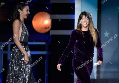 """Gal Gadot, Patty Jenkins. Gal Gadot, left, and Patty Jenkins walk on stage to accept the award for best action movie for """"Wonder Woman"""" at the 23rd annual Critics' Choice Awards at the Barker Hangar, in Santa Monica, Calif"""