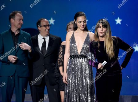 """Gal Gadot, Patty Jenkins. Gal Gadot, center, Patty Jenkins and the crew of """"Wonder Woman"""" accept the award for best action movie at the 23rd annual Critics' Choice Awards at the Barker Hangar, in Santa Monica, Calif"""