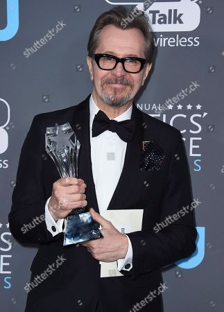 """Gary Oldman poses in the press room with the award for best actor - film for """"The Darkest Hour"""" in the press room at the 23rd annual Critics' Choice Awards at the Barker Hangar, in Santa Monica, Calif"""