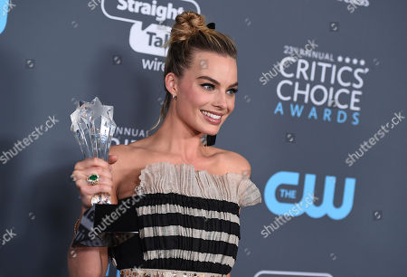"""Margot Robbie, winner of the award for best actress in a comedy for """"I, Tonya"""", poses in the press room at the 23rd annual Critics' Choice Awards at the Barker Hangar, in Santa Monica, Calif"""