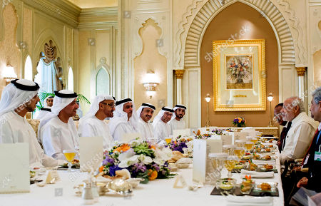 Mohamed bin Zayed Al Nahyan, Narendra Modi, Mansour bin Zayed Al Nahyan, Hazza bin Zayed Al Nahyan, Saif bin Zayed Al Nahyan, Anwar bin Mohamed Gargash, Mohamed Mubarak Al Mazrouei. In this photo made available by Crown Prince Court, Abu Dhabi, Sheikh Mohamed bin Zayed Al Nahyan, Crown Prince of Abu Dhabi and Deputy Supreme Commander of the UAE Armed Forces, third left, talks to Narendra Modi, Prime Minister of India, right, at the Emirates Palace Hotel in Abu Dhabi, United Arab Emirates, . The rest at the table are hosts for a lunch reception with Modi, including Sheikh Mansour bin Zayed Al Nahyan, UAE Deputy Prime Minister and Minister of Presidential Affairs, left, Sheikh Hazza bin Zayed Al Nahyan, UAE National Security Advisor and Vice Chairman of the Abu Dhabi Executive Council, second left, Lt. General Sheikh Saif bin Zayed Al Nahyan, UAE Deputy Prime Minister and Minister of Interior, fourth left, Sheikh Abdullah bin Zayed Al Nahyan, UAE Minister of Foreign Affairs, fifth left, Dr Anwar bin Mohamed Gargash, UAE Minister of State for Foreign Affairs, sixth left, and Mohamed Mubarak Al Mazrouei, Undersecretary of the Crown Prince Court of Abu Dhabi, seventh left