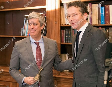 Outgoing leader Jeroen Dijsselbloem, right, of the Netherlands formally hands over power of the so-called eurogroup, in the form of a symbolic bell, to Portugal's Mario Centeno during a ceremony in Paris, Friday, Jan.12, 2018. The euro zone's new leader says he hopes to use his term to bring the 19 countries that use the currency closer together and toughen their ability to weather future crises