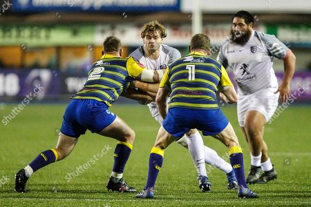 Richie Gray of Toulouse is tackled by Matthew Rees and Gethin Jenkins of Cardiff Blues