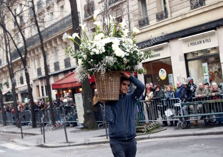 A man delivers a huge bouquet of flowers outside the Montmartre cemetery for French singer France Gall's burial in Paris, Friday, Jan.12, 2018. French pop singer France Gall, who shot to fame in the 1960s by winning the Eurovision Song Contest then produced hits and sold millions of albums over a four-decade career, died last Sunday. She was 70