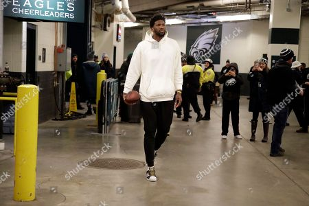 Philadelphia 76ers' Joel Embiid walks through the tunnel before an NFL divisional playoff football game between the Philadelphia Eagles and the Atlanta Falcons, in Philadelphia