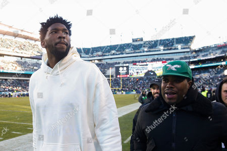 Philadelphia 76ers' Joel Embiid looks on from the sidelines prior to an NFL divisional playoff football game between the Atlanta Falcons and the Philadelphia Eagles, in Philadelphia. Philadelphia won 15-10