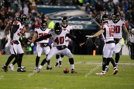 Atlanta Falcons' Derrick Coleman (40) holds back teammates not to touch the punted ball during the first half of an NFL divisional playoff football game against the Philadelphia Eagles, in Philadelphia. Philadelphia won 15-10