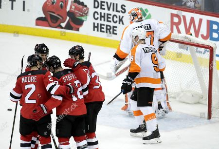 New Jersey Devils players celebrate a goal by right wing Drew Stafford (18) as Philadelphia Flyers goaltender Brian Elliott (37) and defenseman Ivan Provorov (9), of Russia, look on during the third period of an NHL hockey game, in Newark, N.J