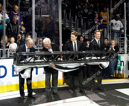 Stock Picture of Rogie Vachon, Pete Weber, Luc Robitaille, Rob Blake. A banner honoring Los Angeles Kings broadcasting legend and Hockey Hall of Famer Bob Miller is lifted by, left to right, former King goalie Rogie Vachon, former broadcasting partner Pete Weber, currently with the Nashville Predators, president of the Kings, Luc Robitaille, and former King Rob Blake before an NHL hockey game against the Anaheim Ducks in Los Angeles