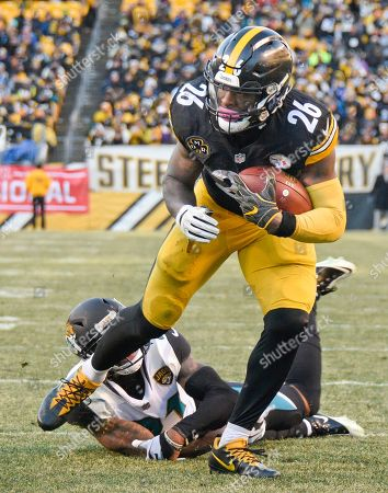 LeVeon Bell, A J Bouye. Pittsburgh Steelers running back Le'Veon Bell (26) heads for the end zone after slipping a tackle by Jacksonville Jaguars cornerback A.J. Bouye (21) after taking a pass from quarterback Ben Roethlisberger during the second half of an NFL divisional football AFC playoff game in Pittsburgh