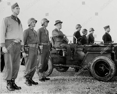 Franklin D. Roosevelt, Mark W. Clark, Reuben H. Tucker, Joseph B. Crawford, William B. Kellogg, Thomas F. Gould. In this photo provided by the U.S. Air Force, flanked by newly decorated officers wearing the Distinguished Service Cross, President Franklin D. Roosevelt reviews American troops in Sicily, during his visit there following the Cairo and Tehran conferences, . From left: Lt. Gen. Mark W. Clark; Col. Reuben H. Tucker; Lt. Col. Joseph B. Crawford; the president; Lt. William B. Kellogg; Lt. Thomas F. Gould; and an unidentified officer