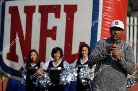 Pro Football Hall of Famer Anthony Munoz, who played for the Cincinnati Bengals, speaks to children as Oakland Raiders cheerleaders look, during an NFL-sponsored event promoting physical activity in Mexico City, . The NFL's Play 60 campaign pushes children to be active 60 minutes a day to avoid childhood obesity. The Raiders play the Houston Texans on Monday