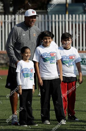 Pro Football Hall of Famer Anthony Munoz, who played for the Cincinnati Bengals, poses for a picture with young fans during an NFL-sponsored event promoting physical activity in Mexico City, . The NFL's Play 60 campaign pushes children to be active 60 minutes a day to avoid childhood obesity