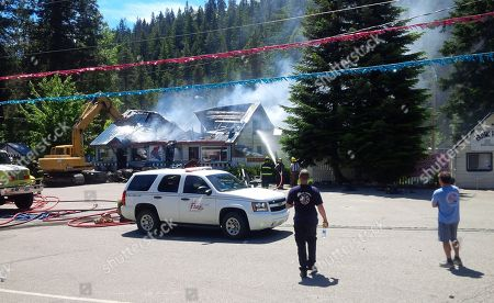 """This, photo provided by Trooper Brian Moore of the Washington State Patrol shows crews hosing down the remains of the 59er Diner near Leavenworth, Wash. A weekend blaze destroyed the popular restaurant. Fire crews from multiple agencies were called to the scene. Washington State Trooper Brian Moore said the diner was a """"total loss"""