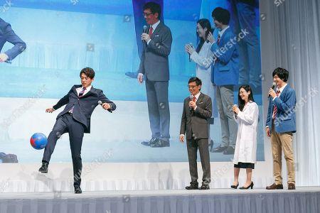 Japanese actor Ryoma Takeuchi (L) shows his soccer skills