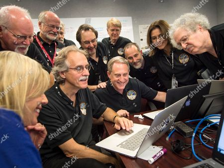 New Horizons Pluto Flyby. In this photo provided by NASA, members of the New Horizons team and embedded journalist standing left, Jeff Moore, science team, NASA Ames Research Center, Randy Gladstone science team Southwest Research Institute (SwRI), Andy Chaikin, science writer, Willam Lewis, science writer, Will Grundy, science team, Lowell Observatory; Maria Stothoff, media relations, Johns Hopkins University Applied Physics Laboratory (APL), Steve Maran, science writer, seated; Laura Cantillo, NASA media relations, left, John Spencer, science team, Southwest Research Institute, and New Horizons Principal Investigator Alan Stern of SwRI gather around a laptop and smile as they review new processed images from the New Horizons spacecraft, at APL in Laurel, Md