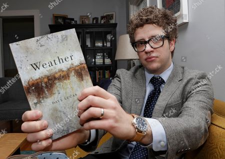 David Lucas holds up his book, Weather, in his home in Cleveland Heights, Ohio. Lucas, Ohio's new poet laureate, says he hopes to celebrate the legacy of poetry in the state and of Ohio poets. Lucas will serve for two years in the position. Lawmakers created the post, which comes with a $5,000 stipend, in 2014