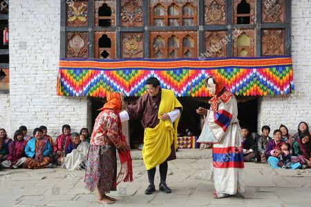 Bhutan King Jigme Khesar Namgyel Wangchuck with performers dressed as an old woman and a hermit at the Khandro Kongsang Tshechu.