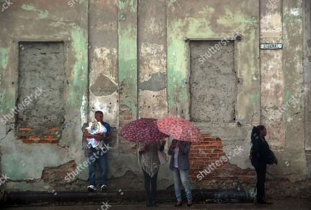 People shelter from the rain in Havana, Cuba, 16 January 2018. The heavy rains in Cuba since September, when hurricane Irma devastated the island, have contributed to reversing the worst drought in the last century, which extended over three years and caused serious water scarcity problems.