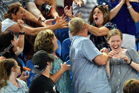 Spectators catch a shoe thrown by Alexandr Dolgopolov of Ukraine during his second round match against Matthew Ebden of Australia at the Australian Open Grand Slam tennis tournament in Melbourne, Australia, 17 January 2018.