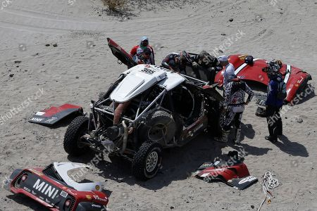 Driver Mikko Hirvonen, of Finland, and co-driver Andreas Schulz, of Germany, work on their Mini during stage 11 of the 2018 Dakar Rally between Belen and Chilecito/Fiambala, Argentina