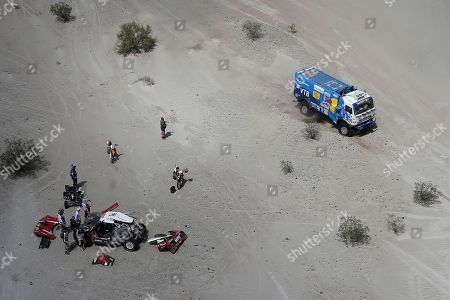 Truck driver Eduard Nikolaev and co-driver Evgeny Yakovlev, both of Russia, race their Kamaz as Driver Mikko Hirvonen, of Finland, and co-driver Andreas Schulz, of Germany, work on their Mini during stage 11 of the 2018 Dakar Rally between Belen and Chilecito/Fiambala, Argentina