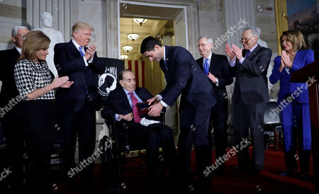 House Speaker Paul Ryan of Wis., presents the Congressional Gold Medal to former Sen. Bob Dole on Capitol Hill, in Washington. Watching from left are Vice President Mike Pence, Rep. Lynn Jenkins, R-Kan., President Donald Trump, Senate Majority Leader Mitch McConnell of Ky., Senate Minority Leader Chuck Schumer of N.Y., and House Democratic Leader Nancy Pelosi of Calif