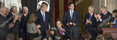 "Former United States Senator Bob Dole (Republican of Kansas) acknowledges the applause in his honor with a ""thumbs-up"" gesture as the Speaker of the United States House Paul Ryan (Republican of Wisconsin) presents the Congressional Gold Medal to him in the Rotunda of the US Capitol. From left to right: US Senator Pat Leahy (Democrat of Vermont), US Senator Pat Roberts (Republican of Kansas), US House Minority Whip Steny Hoyer (Democrat of Maryland), US Vice President Mike Pence, US Representative Lynn Jenkins (Republican of Kansas), US President Donald Trump, Senator Dole, Speaker Ryan, US Senate Majority Leader Mitch McConnell (Republican of Kentucky), US Senate Minority Leader Chuck Schumer (Democrat of New York), and US House Minority Leader Nancy Pelosi (Democrat of California)."