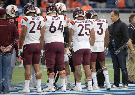 Camping World CEO Marcus Lemonis, right, helps conduct the coin toss with captains for Oklahoma State and Virginia Tech before the Camping World Bowl NCAA college football game, in Orlando, Fla