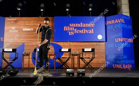 Kevin Kane, technical production manager of the Sundance Institute, mops the stage before the opening day press conference on the first day of the 2018 Sundance Film Festival, in Park City, Utah
