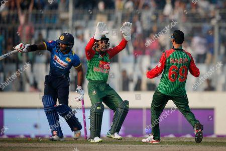 Nasir Hossain, Mushfiqur Rahim, Kusal Perera. Bangladesh's Nasir Hossain, right, celebrates with his teammate wicketkeeper Mushfiqur Rahim, center, the dismissal of Sri Lanka's Kusal Perera, left, during the Tri-Nation one-day international cricket series in Dhaka, Bangladesh