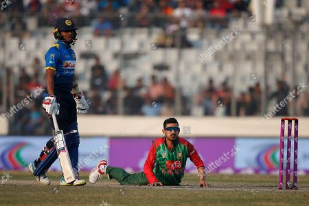 Stock Image of Bangladesh's Nasir Hossain, right, drives to stop the ball as he bowls against Sri Lanka during the Tri-Nation one-day international cricket series in Dhaka, Bangladesh