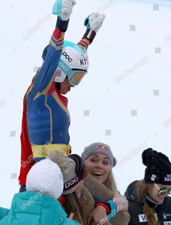 United States' Julia Mancuso, top, wearing a Wonder Woman suit, is celebrated by members of the US ski team including Lindsey Vonn, after completing an alpine ski, women's World Cup downhill, in Cortina D'Ampezzo, Italy, Friday, Jan.19, 2018. Mancuso announced she will retire from skiing after a goodbye run in a World Cup downhill Friday
