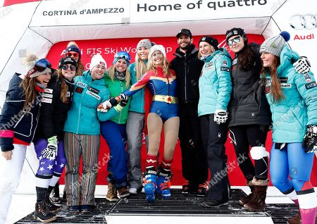United States' Julia Mancuso, center wearing a Wonder Woman suit, is celebrated by the US ski team at the end of an alpine ski, women's World Cup downhill, in Cortina D'Ampezzo, Italy, Friday, Jan.19, 2018. Four-time Olympic medalist Mancuso announced she will retire from skiing after a goodbye run in a World Cup downhill Friday