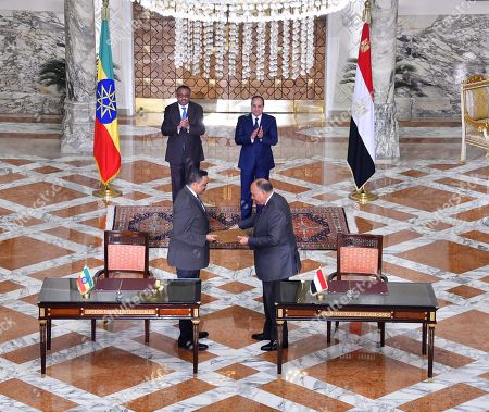Egyptian Foreign Minister Sameh Shoukry and his Ethiopian counterpart Workneh Gebeyehu exchanging memorandums as Egyptian President Abdel Fattah al-Sisi and Ethiopia Prime Minister Hailemariam Desalegn watch during a ceremony at the Presidential Palace in the capital Cairo